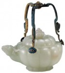 An imperial jade pot with a handle, used by Emperor Jiaqing (1796—1820) of the Qing Dynasty with a height of 10.5 cm and a diameter at the opening of 8.5 cm. The handle height is 10.4 cm